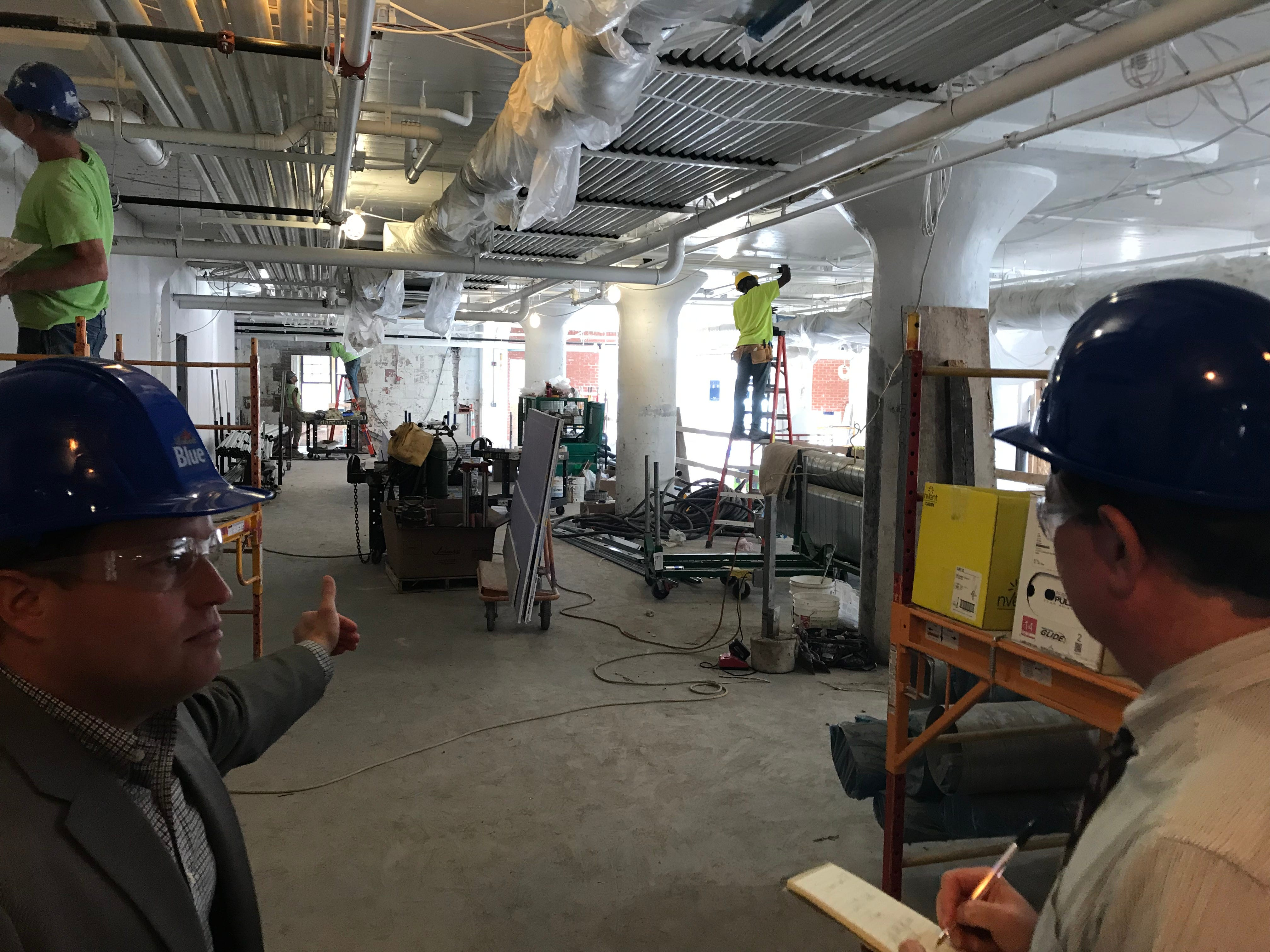 Don Heins, left, head of communications for Pegula Sports and Entertainment, leads a tour through the Labatt Brew House in Buffalo.