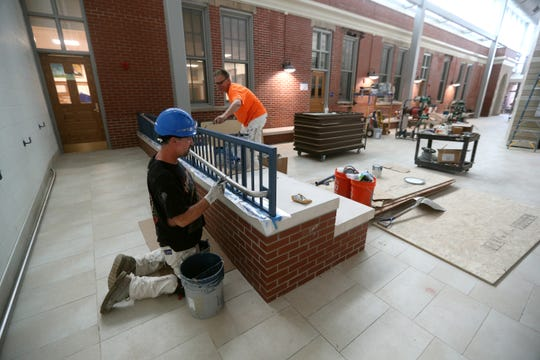 Workers finish up painting in an addition at School 16.