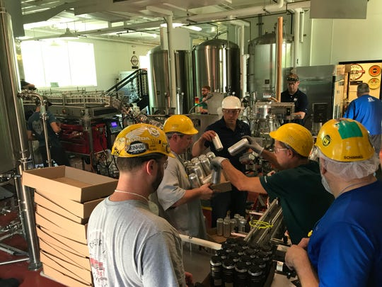 Workers from Genesee and Iron Heart Canning work to can the brewery's new Bourbon Barrel-Aged Stout Tuesday inside the Genesee Brew House.