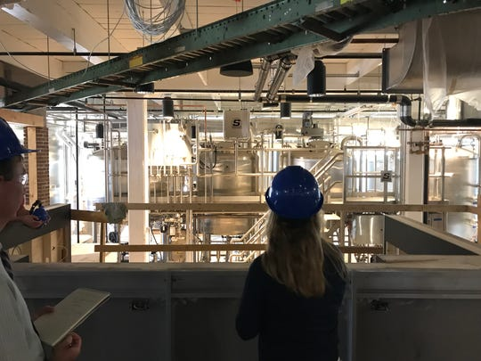 Brinn Johnson, director of retail strategy and brand development for Labatt USA, looks over the tasting room area at the new Labatt Brew House in Buffalo.