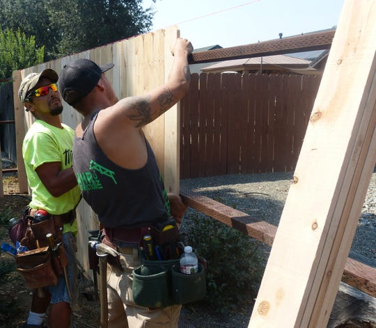 Ben Connor, left, and Kyle Nyberg, who both work for Lahr Construction were busy building a new fence at the home of fallen Redding firefighter Jeremy Stoke.