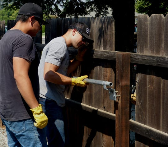 Redding firefighters Brian Nakatani, left, and Kody Hansen help dismantle what remained of the old fence to make way for a new one.