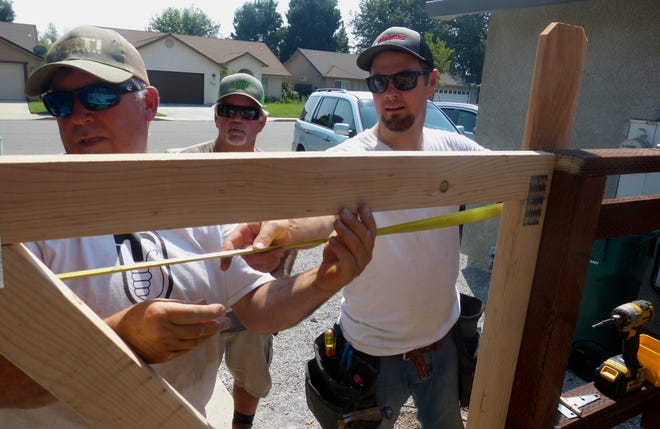 Sam Dawson, right, helps build a new front gate and fence with Sean Hudson, left, and Jeff Lahr.