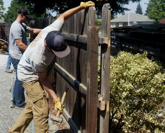 Redding firefighters Brian Nakatani, Kody Hansen and Kyle Foott help tear down the old fence.