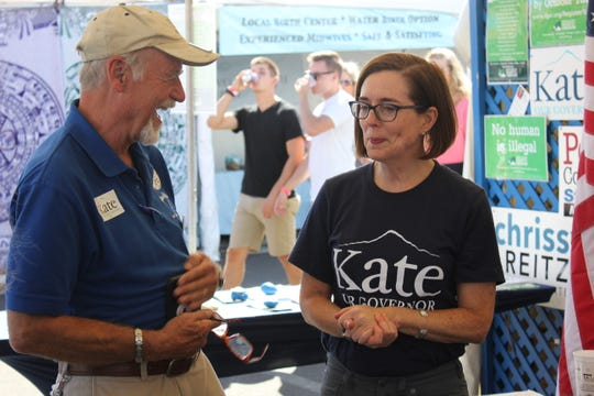 Oregon Gov. Kate Brown speaks with volunteers at the Democratic Party of Oregon's booth at the Oregon State Fair on Monday, Sept. 3, 2018.