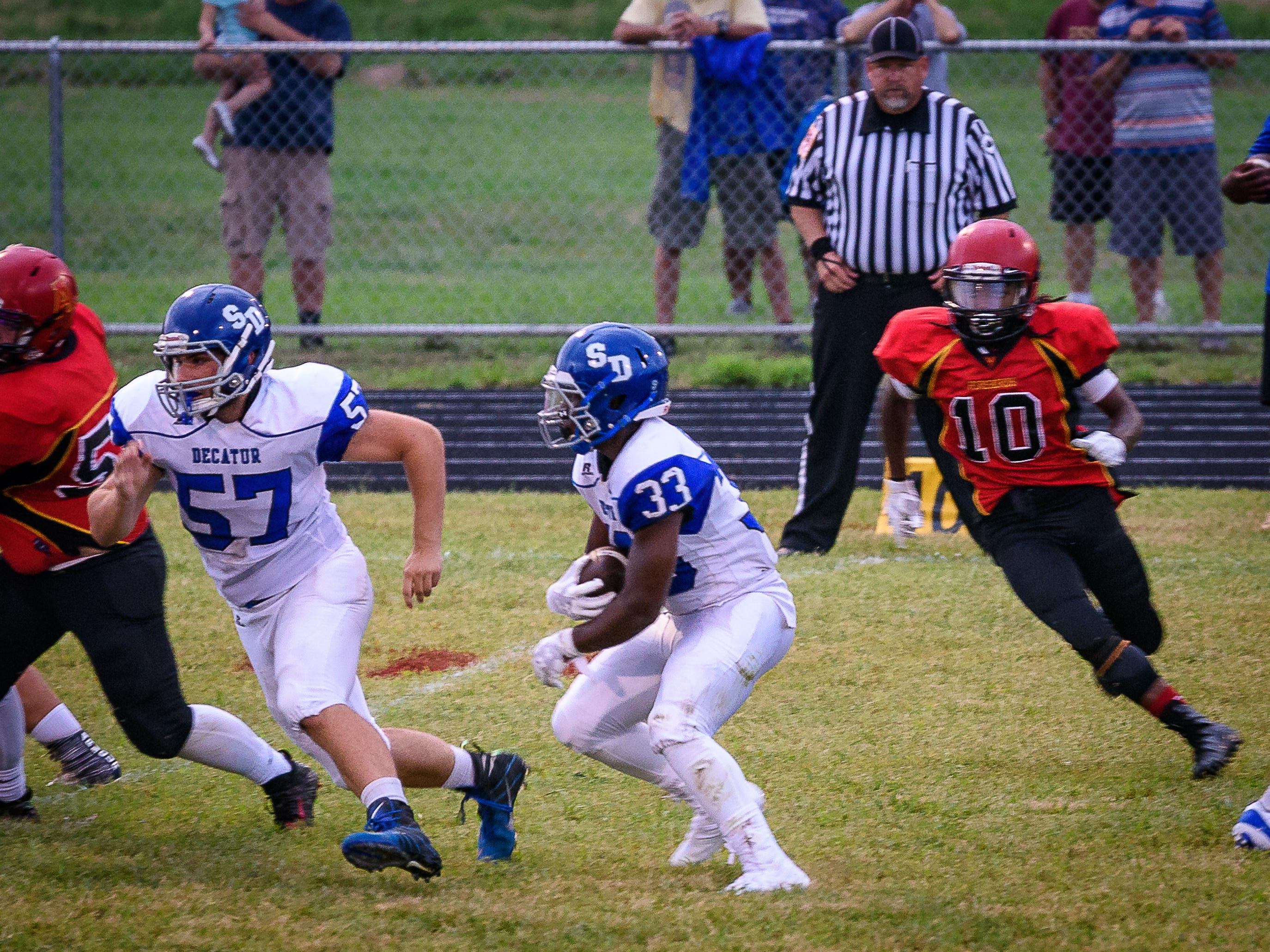 Decatur's Devin Waters, No. 33, tries to break through on his return run as teammate Conner Carpenter leads the way. Arcadia's William Scarborough gives chase.