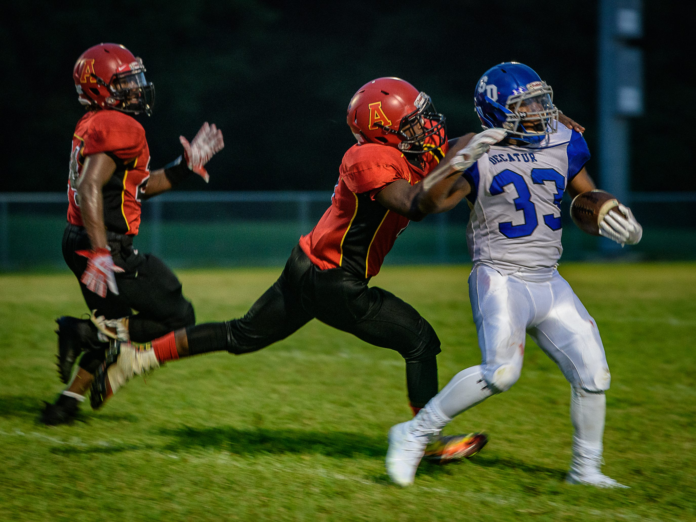 Arcadia's Kam Downing and Bryden Bibbins try to take down Decatur's Devin Waters.