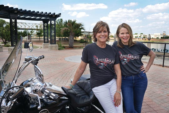 Feist-Weiller Cancer Center Boots & Bikers Life Savers 2018 Co-Chairs Mary O'Neal and Dr. Destin Black   showing off a motorcycle at a photo op on the riverfront.