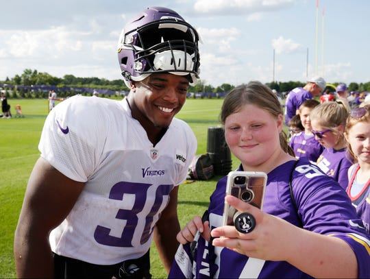 Minnesota Vikings fullback C.J. Ham takes a selfie with a fan at the end of NFL football practice in Eagan, Minn., Monday, July 30, 2018. (AP Photo/Andy Clayton-King)