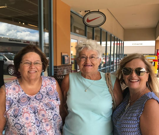 "Sue Peachley, right, of Pratt, Kansas, called her husband from inside the Nike store to ask if he wanted her to buy him anything. He said, ""Hell no.""  Peachley is with her mother, Shirley Parrott, center, and her sister Brenda Bowling of Bardstown, Kentucky."