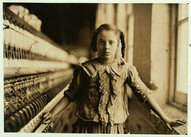 A young spinner in a North Carolina cotton manufacturing company poses for Lewis Hine, the documentary photographer who inspired the creation of laws to ban child labor.