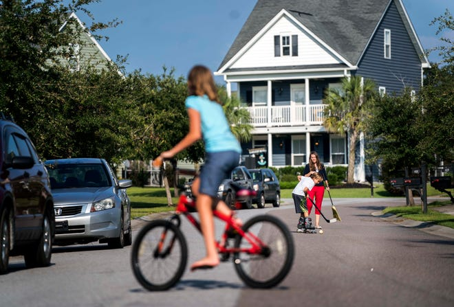 People ride bikes and play on Scrapbook Lane in the Reminisce subdivision.