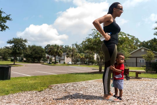Tameka Hyman's daughter, Tia Green, stands with Amir, her 15-month-old, at the Reminisce subdivision park.