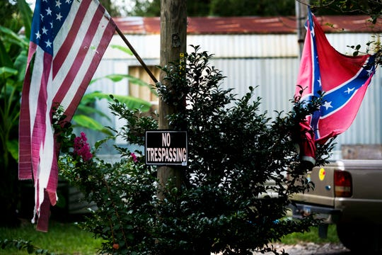 """In an adjacent neighborhood to the Reminisce subdivision, a home displays an American flag and Confederate flag near a sign that says """"No trespassing."""""""