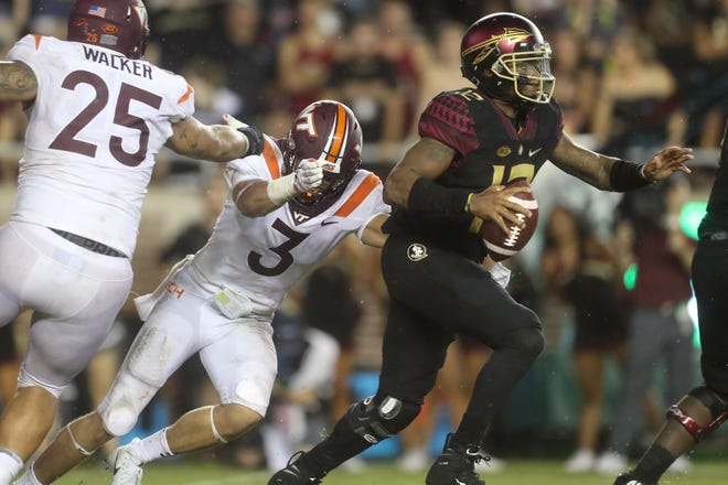 FSU's Deondre Francois is dragged down for a sack by Virginia Tech's Caleb Farley at Doak Campbell Stadium in Tallahassee, Fla. On Monday, Sept 3, 2018.