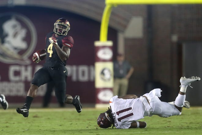 FSU's Khalan Laborn runs away from a diving Houshun Gaines of Virginia Tech for a long gain during their game at Doak Campbell Stadium in Tallahassee, Fla. On Monday, Sept. 3, 2018.