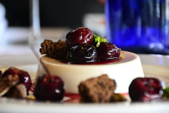 One of Mimi Table's signature desserts is a rosé panna cotta topped with pached cherries, chocolate biscotti, and micro basil.
