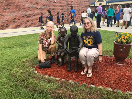 Artist Melinda Cooper, left, and Dr. Marcia Meale sit with a newly unveiled sculpture added to an existing sculpture in celebration of Conley Elementary School's 10 year anniversary.