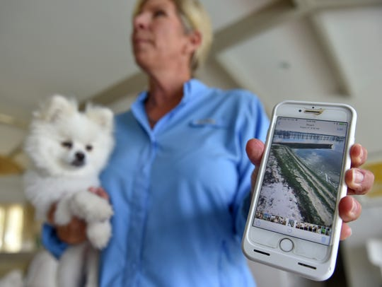 "Becky Harris, with her two-year-old dog Pandora, displays a photo of algae Tuesday, Sept. 4, 2018, in their back yard along the St. Lucie River where Pandora became sick after taking a bite out of a dead catfish on Aug. 26 in Stuart. ""The most important thing is to keep them away from the water,"" Harris said. ""Leash your dogs and keep them away from the water."""
