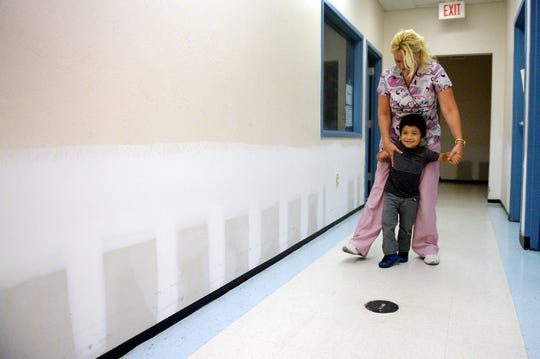 Michelle Barron, a physical therapist assistant, helps Jesus Estrada, 3, walk Tuesday, September 4, 2018, down a hallway at PATCHES PPEC Medical Daycare that still needs to be painted a year after Hurricane Irma flooded the Orange Blossom Business Center in Fort Pierce. The daycare provides services for children with complex medical needs.