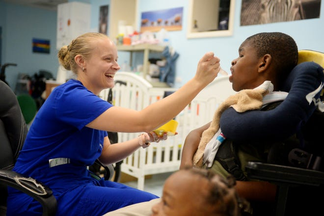 """Jessica Castro, a licensed practical nurse, helps feed Daishaun Owens Tuesday, Sept. 4, 2018 at PATCHES PPEC Medical Daycare in Fort Pierce. After Hurricane Irma, about 60 children with complex medical needs were displaced. """"Pretty much everything that was wooden we had to replace,"""" said Gail Steward, administrator for the day care. """"But, it takes time and money, and we're a non-profit, so we rely on volunteers and donations to get things back the way they were."""" About two feet from the floor of every wall had to be cut out and replaced due to flooding and some areas still need painting."""