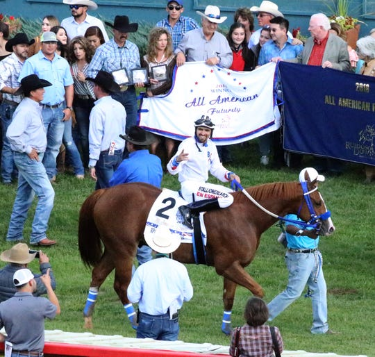 Jockey Raul Ramirez Jr., aboard Apocalyptical Jess, acknowledges the crowd in the winner's circle after finishing first in the 60th All American Futurity Monday at Ruidoso Downs Racetrack and Casino.