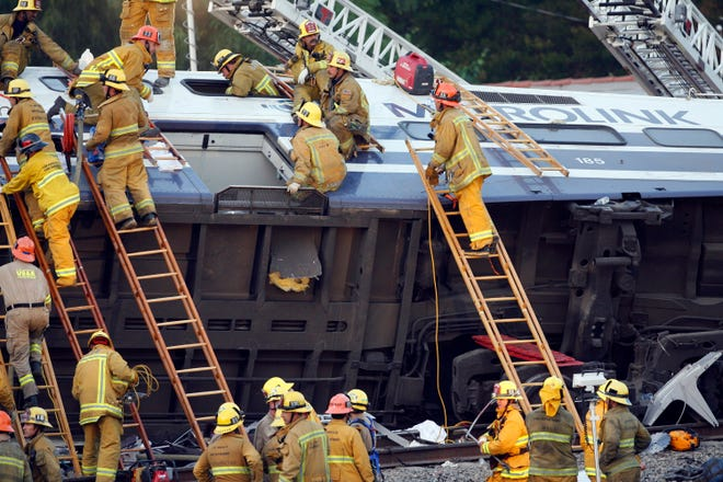 Firefighters work to rescue trapped passengers in the aftermath of the Sept. 12, 2008, crash in Chatsworth between a Metrolink commuter train and a Union Pacific freight train that killed 25 people. (AP Photo/Damian Dovarganes)
