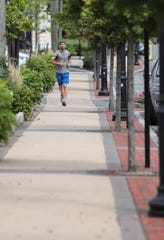 A man jogs on the sidewalk along Main Street in New City on Saturday, September 1, 2018.