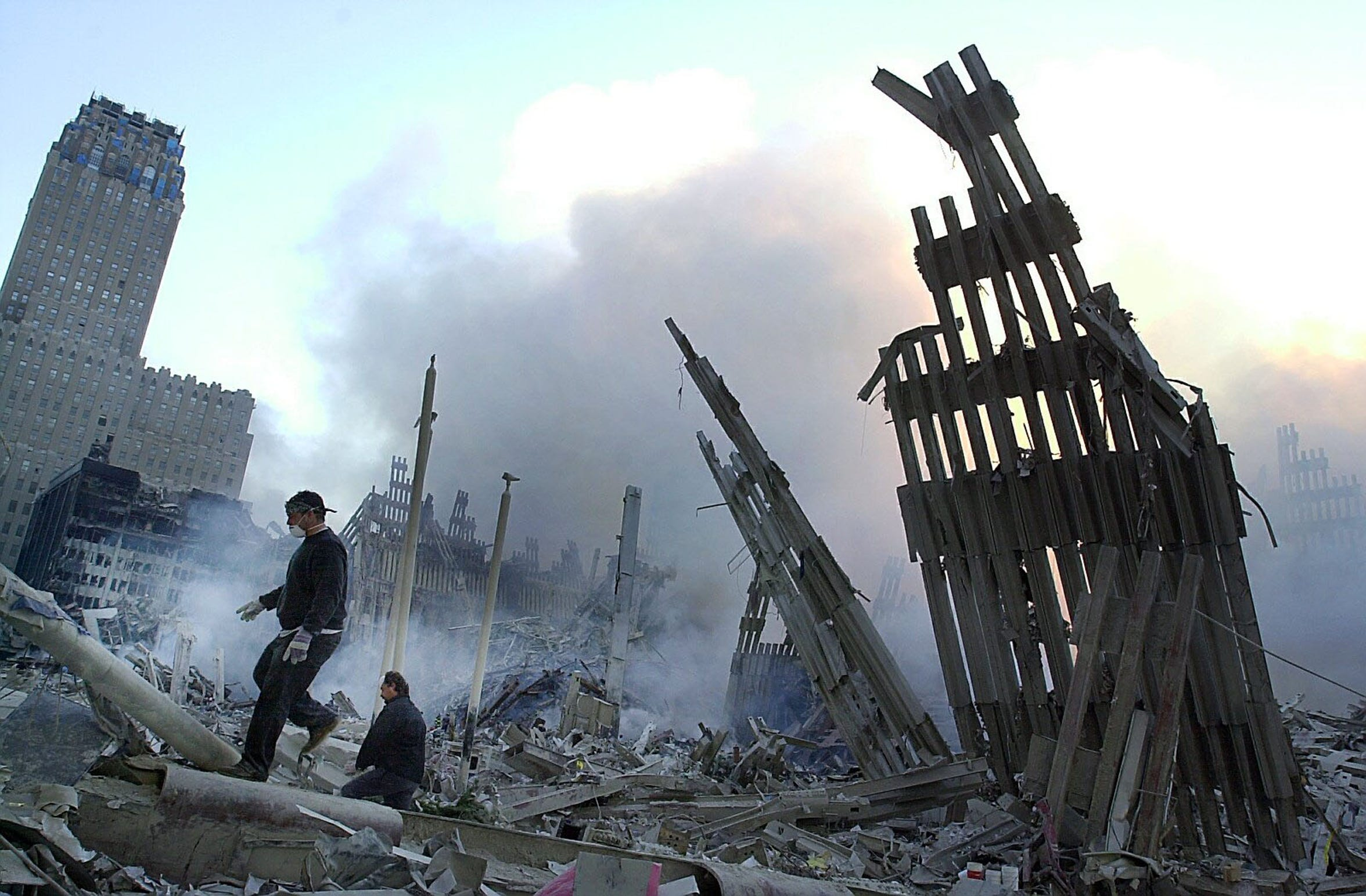 The twisted silhouette of World Trade Center buildings loom above rescue workers at Ground Zero on Sept. 13, 2001.