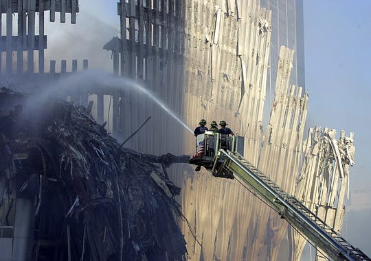 FDNY Tower Ladder 15 extinguishes small pockets of fire amidst the ruins and rescue efforts at  Ground Zero on Sept. 12, 2001.
