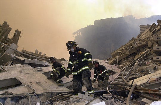 New York City firefighters maneuver around the debris at Ground Zero on Sept. 11, 2001 during a search for victims and survivors.