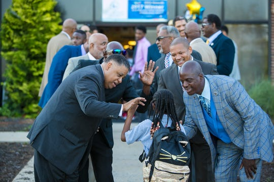 Professional black men in suits and members of the Canaan Baptist Church greet students at Charter School of New Castle as they arrive for school. The idea is to model what success looks like for students who come from some of the roughest neighborhoods in Wilmington.