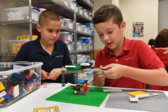 Travis Mulder, left, and Myles Tate attach Lego building blocks as they work on a STEAM curriculum challenge to build a scaled-down amusement park ride during class at Christ Academy.