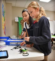 Rebecca Vu and Madison Smith, right, explore the robotic workings of Milo the Science Rover during the STEAM Lab class at Christ Academy.