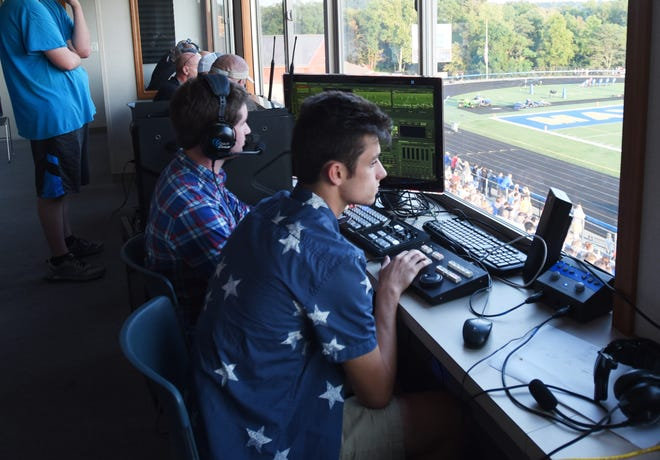 Maysville High School students Dakota Fisher, left, and J.T. Stephenson run the scoreboard display during Friday night's Maysville football game against Sheridan.