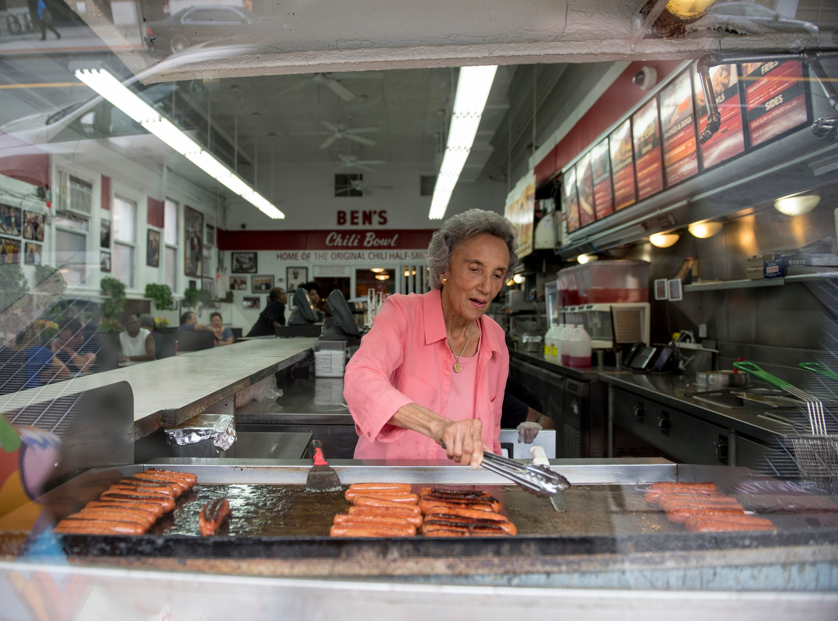 Virginia Ali, 85, owner and co-founder of Ben's Chili Bowl, rotates hotdogs on the grill to be served to customers. Virginia and her late husband Ben opened their doors in August, 1958 and continue to grow their business.