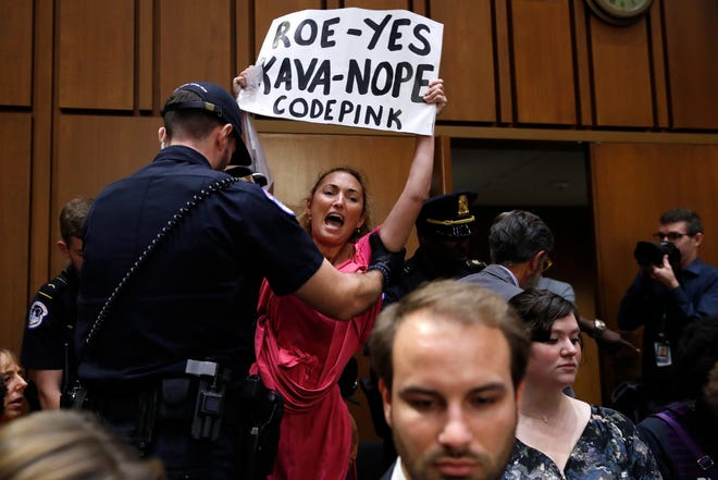 A woman stands and voices her opposition to Supreme Court nominee Brett Kavanaugh, during a Senate Judiciary Committee confirmation hearing on his nomination for Supreme Court, on Capitol Hill, Tuesday, Sept. 4, 2018, in Washington.  (AP Photo/Jacquelyn Martin) ORG XMIT: DCJM102