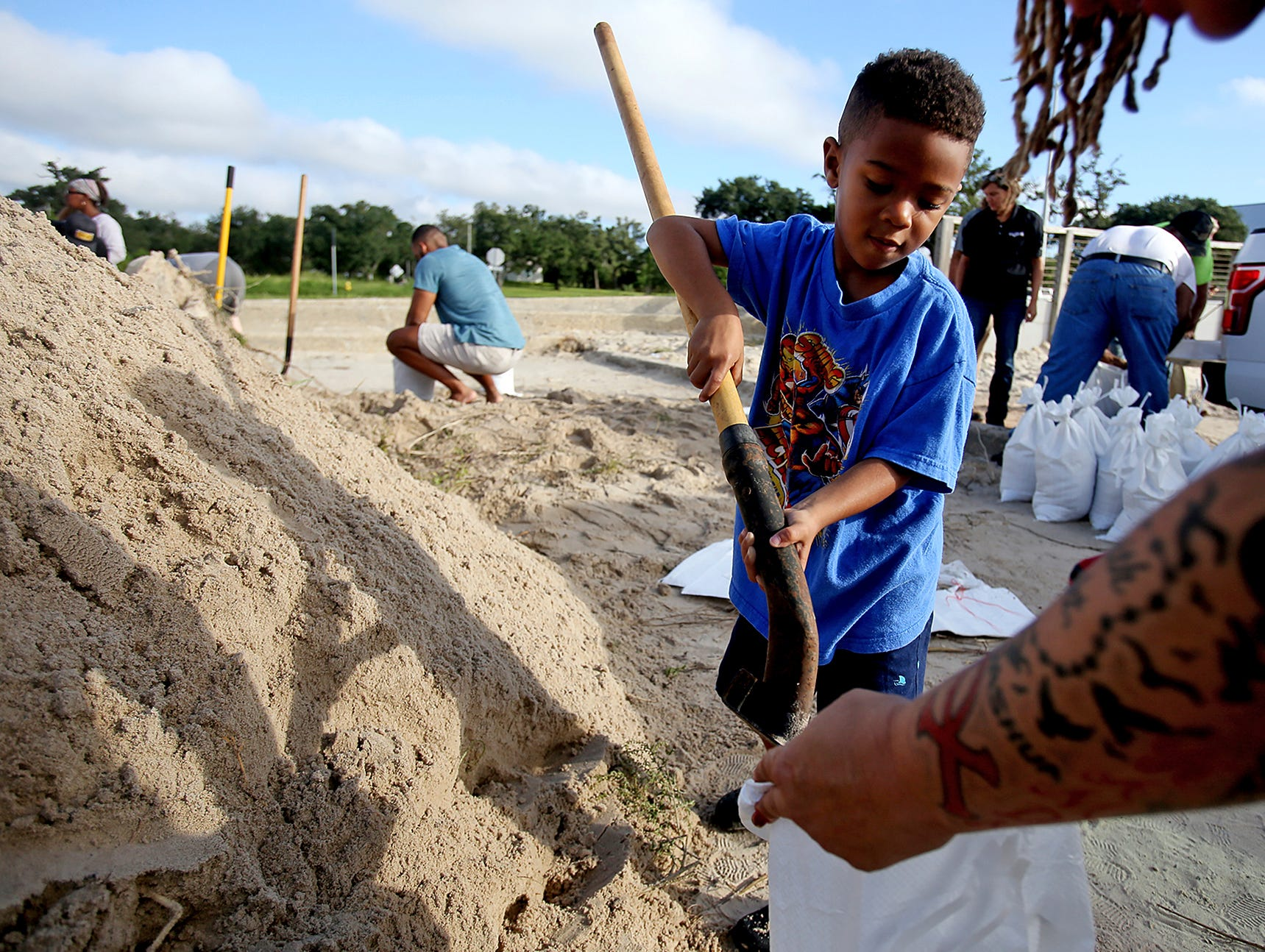 Kamdn Boose, 4, helps his family fill sandbags at Long Beach Harbor, Tuesday, Sept. 4, 2018, in Long Beach, Miss., in advance of Tropical Storm Gordon.