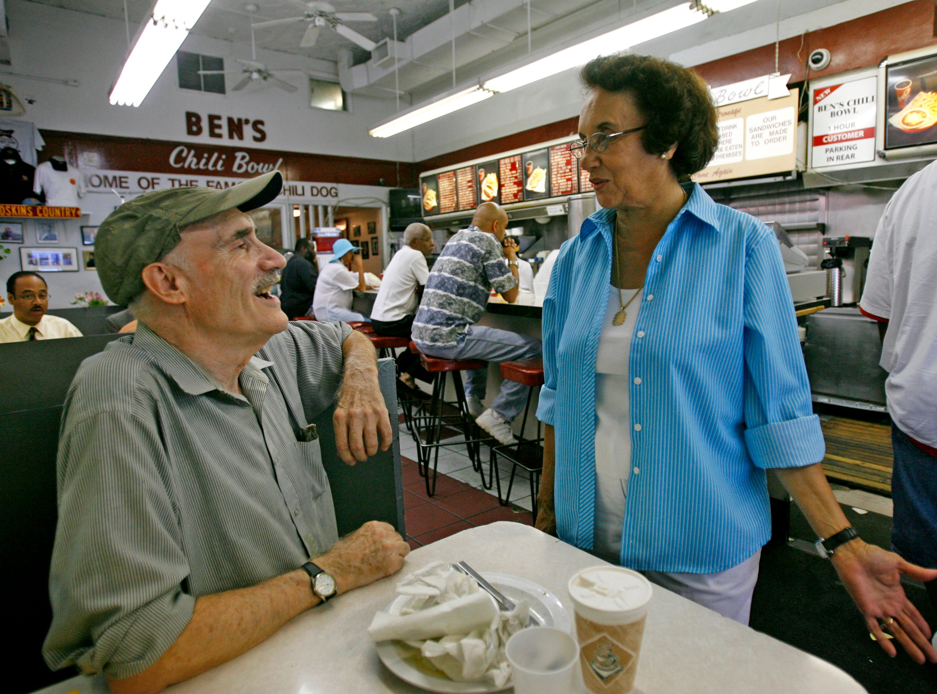 "Dave MacDonald, 68, of Washington, left, visits with Virginia Ali, 74, co-owner of Ben's Chili Bowl, in Washington, Aug. 1, 2007. ""I like the atmosphere and I like the people who come here,"" says MacDonald, ""there are a lot of new people coming but the atmosphere is the same."""