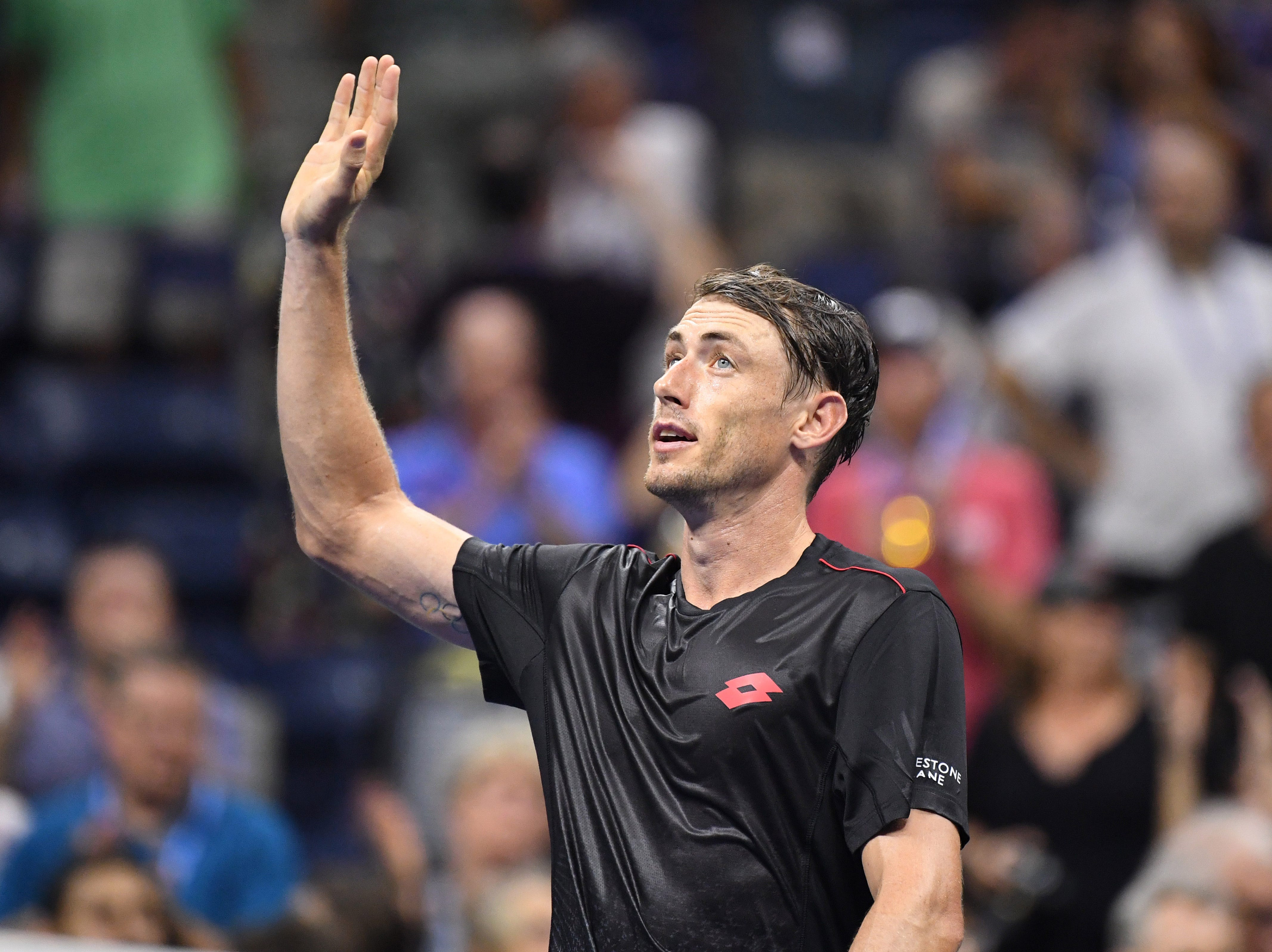 John Millman celebrates after defeating Roger Federer in the fourth round.