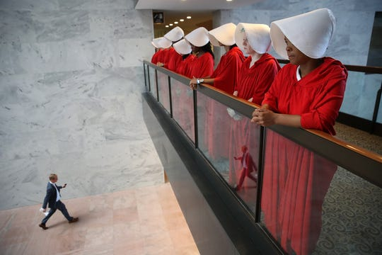 WASHINGTON, DC - SEPTEMBER 04:  Protesters dressed in The Handmaid's Tale costume, protest outside the hearing room where Supreme Court nominee Judge Brett Kavanaugh will testify before the Senate Judiciary Committee during his Supreme Court confirmation hearing in the Hart Senate Office Building on Capitol Hill September 4, 2018 in Washington, DC. Kavanaugh was nominated by President Donald Trump to fill the vacancy on the court left by retiring Associate Justice Anthony Kennedy.
