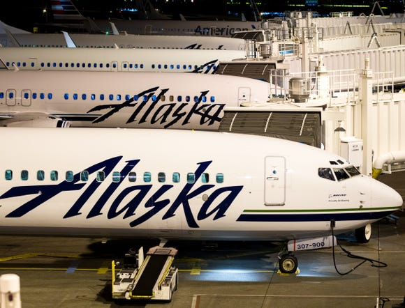 Alaska Airlines jets line up for departure early in the morning at Seattle-Tacoma International Airport on Nov. 11, 2016.