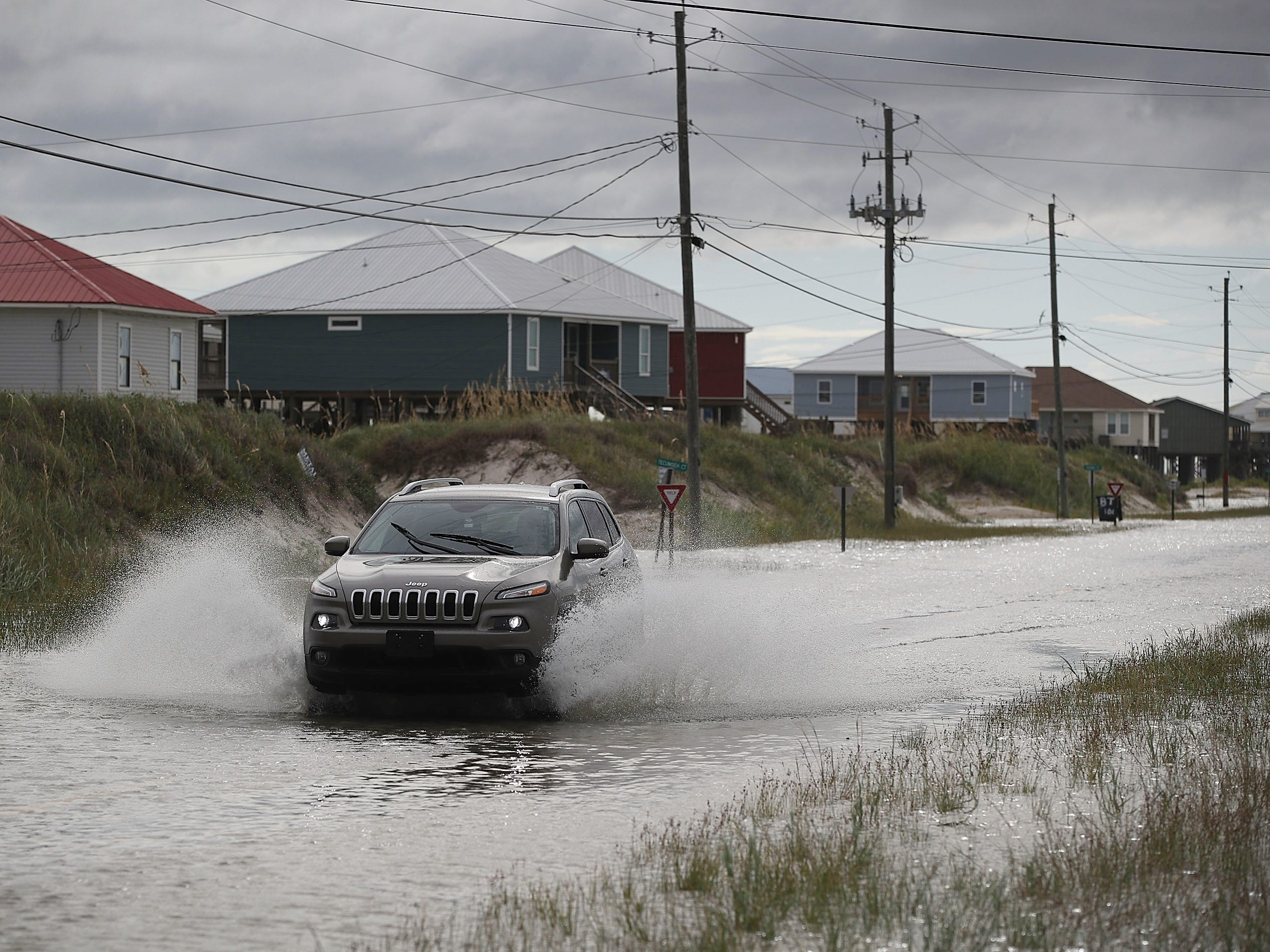 DAUPHIN ISLAND, AL - SEPTEMBER 04:  A vehicle drives along a flooded street caused by the approaching Tropical Storm Gordon on September 4, 2018 in Dauphin Island, Alabama.  Gordon heads for the northern Gulf Coast area as a strong tropical storm and could possibly strengthen into a Category 1 hurricane.  (Photo by Joe Raedle/Getty Images) ORG XMIT: 775220251 ORIG FILE ID: 1026740144