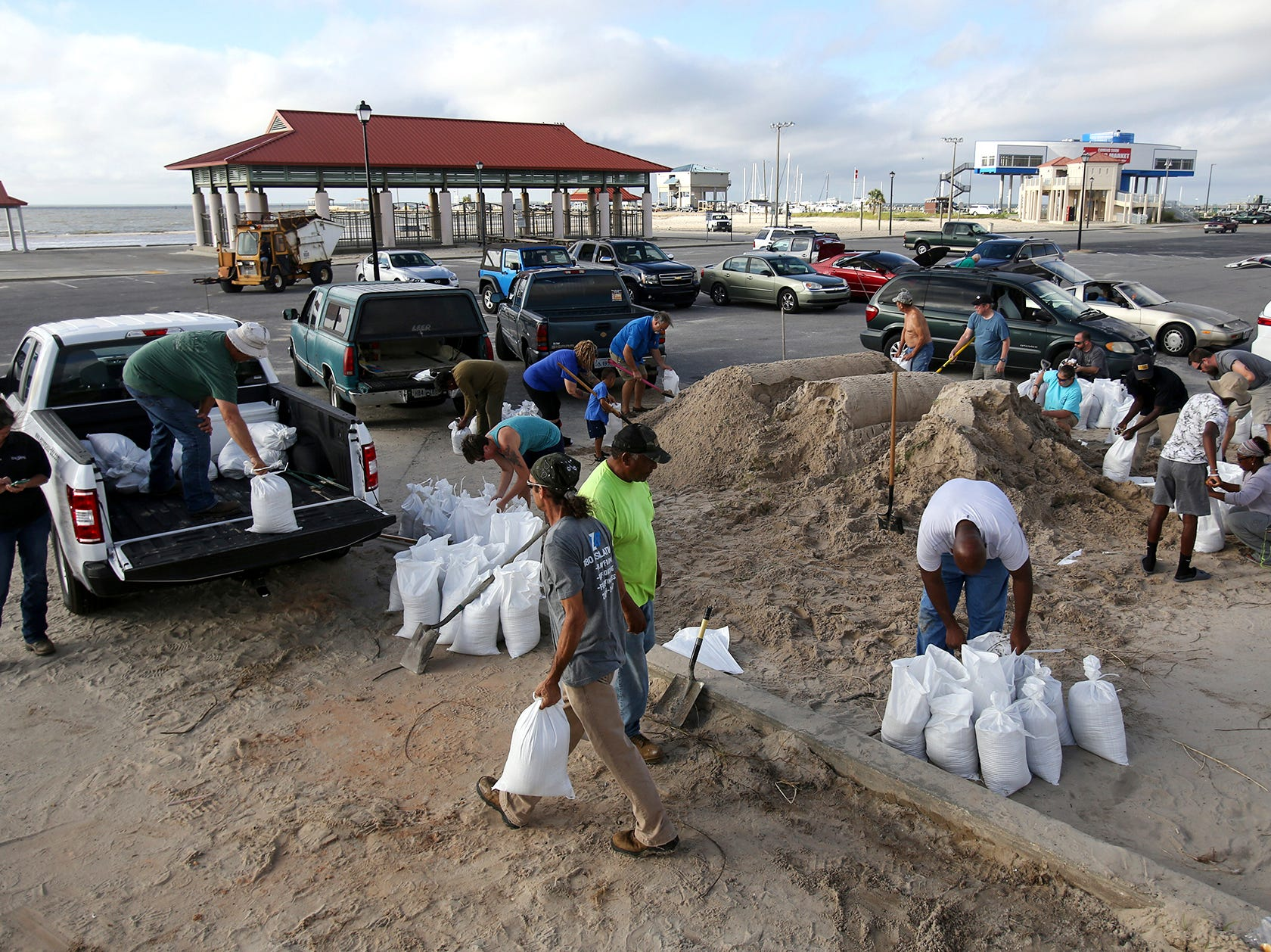 People fill sandbags at Long Beach Harbor, Tuesday, Sept. 4, 2018, in Long Beach, Miss., in advance of Tropical Storm Gordon, which is continuing to strengthen and is expected to become a hurricane late Tuesday when it hits the central U.S. Gulf Coast, including coastal Mississippi.