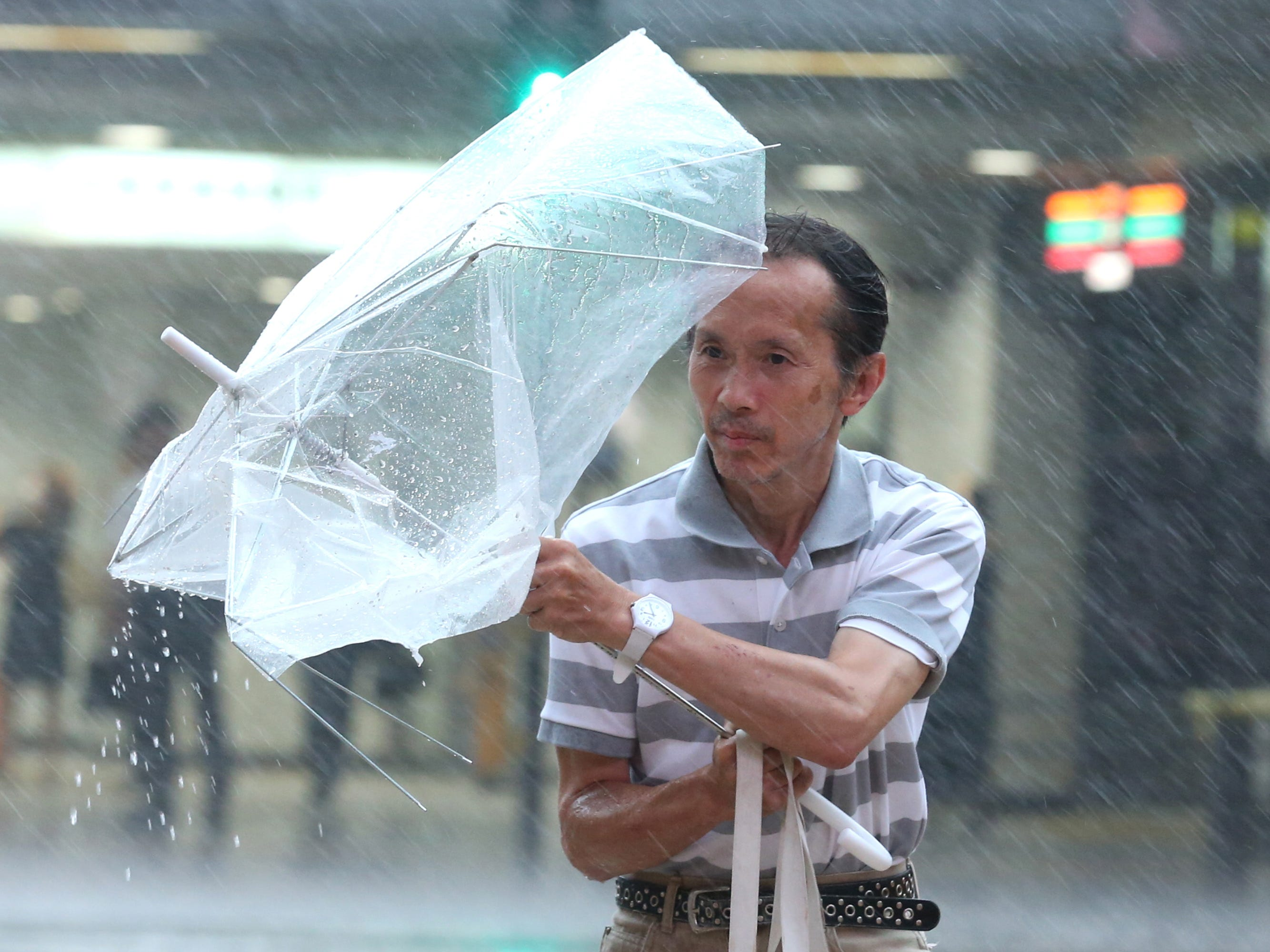 epa06995622 A pedestrian struggles against strong winds and rain generated by typhoon Jebi near Osaka station in Osaka, western Japan, 04 September 2018. Powerful typhoon Jebi made landfall in western Japan disrupting transports due to strong winds and heavy rain.  EPA-EFE/BUDDHIKA WEERASINGHE ORG XMIT: BUD