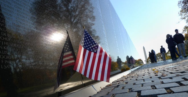 A U.S. flag is seen next to the Vietnam War Memorial as visitors pay their respects on Veterans Day on Nov. 11, 2010 in Washington.