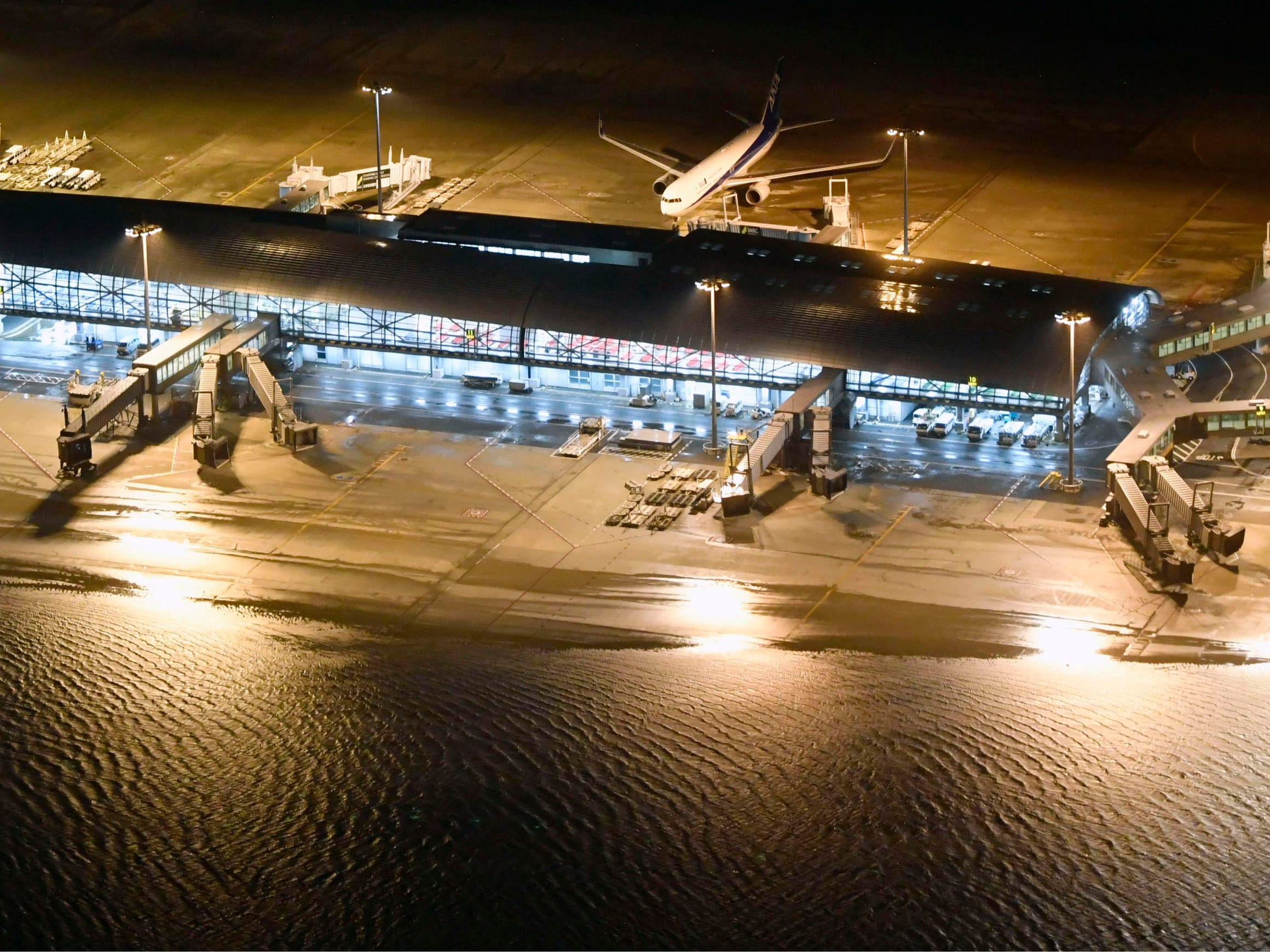 Kansai International Airport partially is flooded by typhoon Jebi in Osaka, western Japan, Tuesday, Sept. 4, 2018. A powerful typhoon blew through western Japan on Tuesday, causing heavy rain to flood the region's main offshore international airport and high winds to blow a tanker into a connecting bridge, disrupting land and air travel. (Nobuki Ito/Kyodo News via AP) ORG XMIT: XEH803