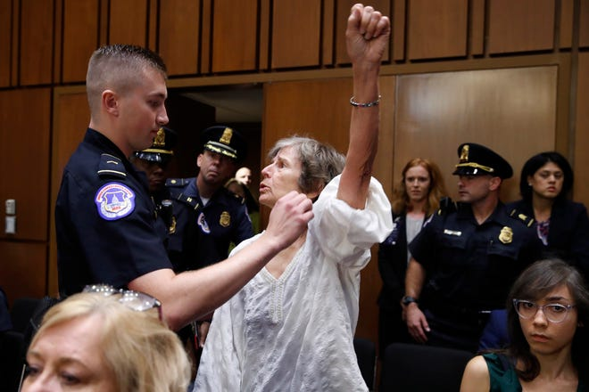 A woman stands and voices her opposition to Supreme Court nominee Brett Kavanaugh, during a Senate Judiciary Committee confirmation hearing on his nomination for Supreme Court, on Capitol Hill, Tuesday, Sept. 4, 2018, in Washington.  (AP Photo/Jacquelyn Martin) ORG XMIT: DCJM101