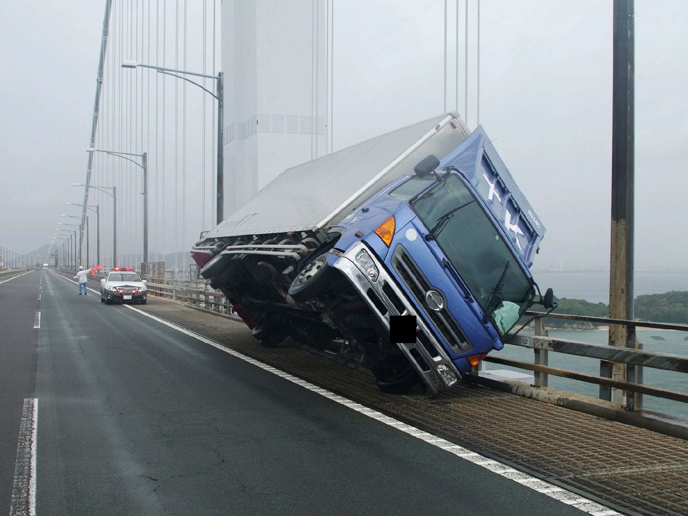 TOPSHOT - This handout photo released by the Kagawa Prefectural Police on September 4, 2018 and received via Jiji Press shows a truck sitting at an angle after being blown over by strong winds caused by Typhoon Jebi on the Seto Ohashi bridge in Sakade, Kagawa prefecture on Japan's Shikoku island. - The strongest typhoon to hit Japan in 25 years made landfall on September 4, the country's weather agency said, bringing violent winds and heavy rainfall that prompted evacuation warnings. (Photo by JIJI PRESS / various sources / AFP) / - Japan OUT / EDITOR'S NOTE: Car's licence plate was digitally blocked by Kagawa prefectural police
