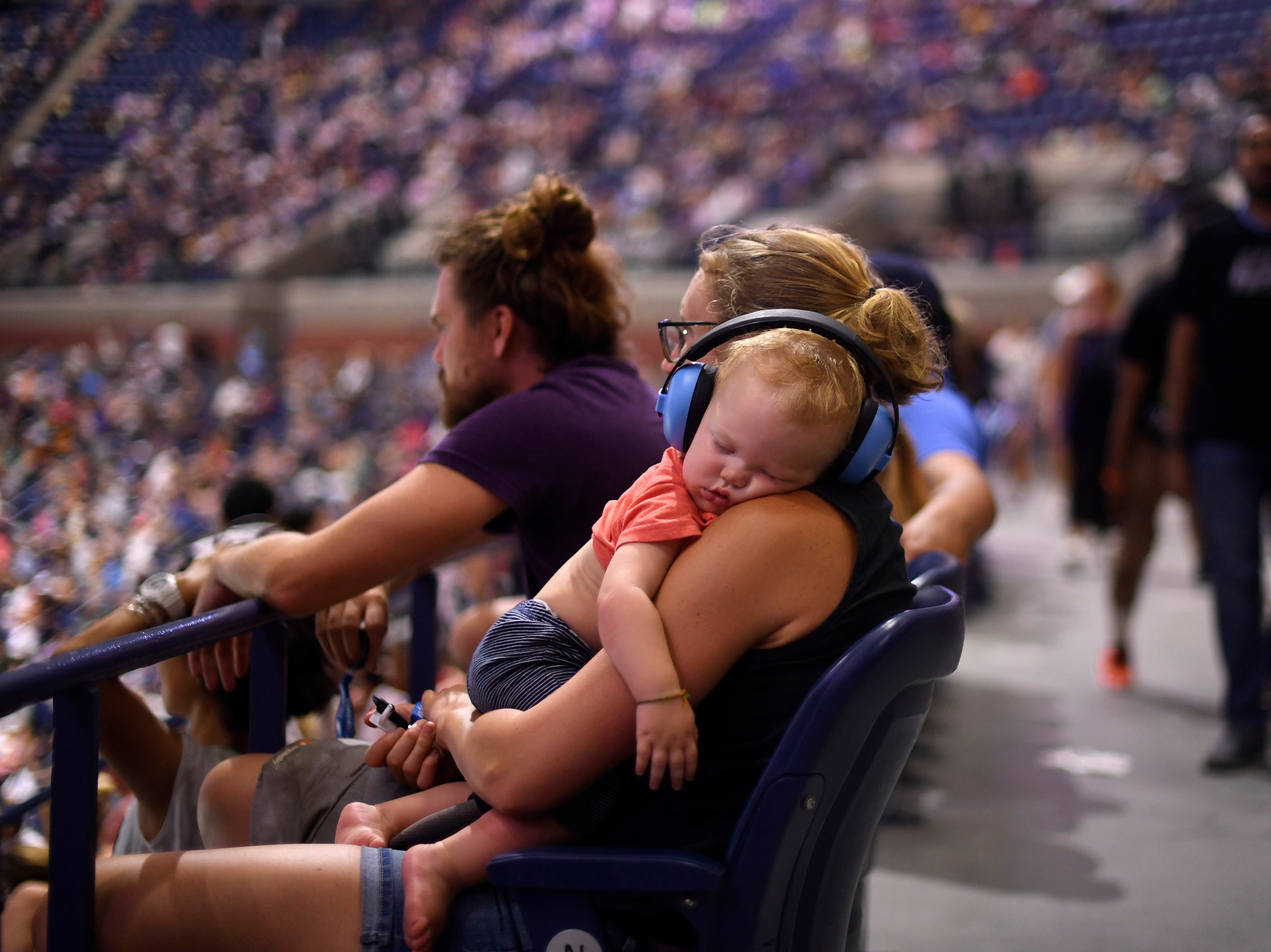 Ten-month-old Holdyn Turner sleeps on the shoulder of mother Kelsey Turner during the match between Roger Federer and John Millman.